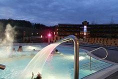 Das Außenbecken der Therme Stegersbach und das Thermenhotel PuchasPlus im Hintergrund bei Nacht