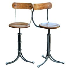 England, 1940.  pair of industrial bar stools with elm seats and back and a metal tripod base.