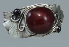 Gingko cuff bracelet with garnets and a large pottery cabochon.