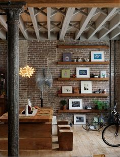 So many elements I love about this....the exposed brick wall, floating wood shelves, wood beams, rustic dining, antique column, lighting fixture....