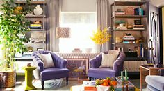 bookcases, purple tufted armchair, green column Bunny Williams side table, gray curtains, and a rattan side table // living rooms