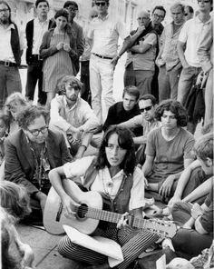Folk singer Joan Baez sits at the corner of Haight and Ashbury and serenades hippies and tourists in a spontaneous concert in San Francisco, on Sept. 22, 1967.