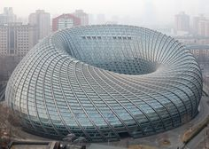 Latticed shell encloses doughnut-shaped television studios in Beijing