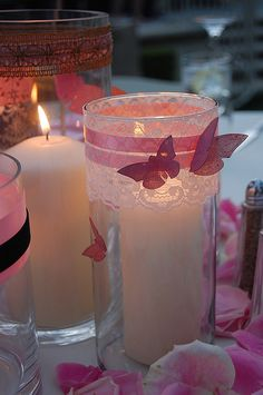 White lace with Purple ribbons and Purple Butterflies on them for the centerpieces. Maybe different shades of candles both pillars and floating.