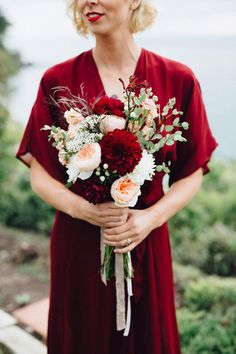Two scarlet dahlias tied this garden rose and carnation arrangement from La Boutique Nostalgie back to this bride's red wedding dress (and her crimson lipstick!).