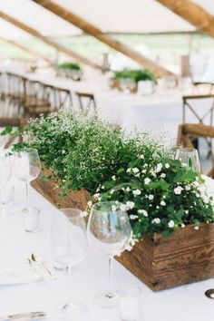 A wispy bunch of white wildflowers and bright green fillers lend an elevated touch to the rustic planters, extending the effect to the clean cut table settings with an inspired contrast.