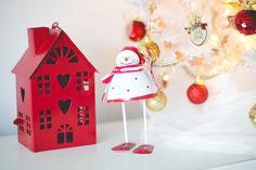 Decoração natalina com casinha vermelha (porta-velas) e boneco de neve branco e vermelho. Decoração com detalhes branco, vermelho e dourado.