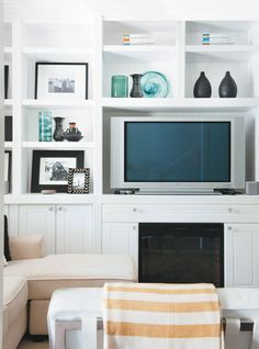 Remotes, manuals and other necessities are concealed in the lower cabinets while family photos and favourite mementoes are framed in the open shelving. #organizing #livingroom