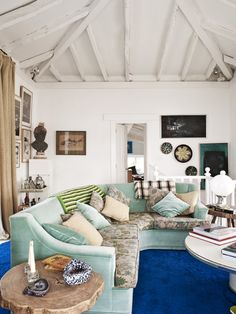 Escape to the Coolest Coastal Home in Spain // Exposed beaming and teal couch