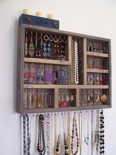 Small wood jewelry organizer stained a grey color. This grey jewelry display case is perfect for a small apartment, dorm room, or closet. Measures 21 wide 16 tall and is 2 5/8 deep. Features 70 stainless steel hooks and a removable piece of cork board that can be used to display post earrings. Jewelry not included. There are many more styles and colors at our main Etsy page. http://www.etsy.com/shop/barbwireandbarnwood?ref=search_shop_redirect I am more than happ...
