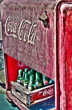 An colorful old, vintage Coca Cola drink cooler/refrigerator with empty Coke bottles in the storage bin below. Photograph processed with HDR (high dynamic range) technique for additional vintage effect. The cooler bears the Drink Coca Cola along with the Coca Cola logo, which also appears on the crate in the bottom of the refrigerator and on the old, green Coke bottles below.
