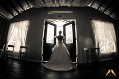 Gorgeous back lit bride in front on chapel doors.  This image in black and white lets the eye focus on the lighting, which give the image it's shape.  Stunning.