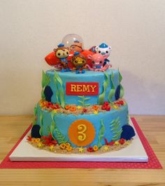 Octonauts Birthday Cake - 8 & 10 inch double layer cakes. Buttercream icing with MMF accents. Toys on top