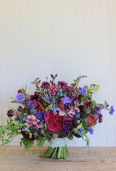 Brides: Purple Bouquet of Anemones and Roses. Bouquet of anemones, garden roses, sweet peas, bachelor buttons, thistles, lupines, baptisia, green wheat, astilbes, muscari, peonies, ferns, and mint, $315, Love 'n Fresh Flowers/Jennie Love
