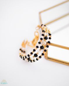 Show off your sophisticated style with this handmade Bangle Bracelet that is made with radiant 22K Gold Plated beads, beautiful glass crystal beads in black, amber and clear and a large gold-plated lobster clasp that effortlessly secures the bracelet to your wrist.