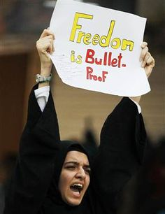 "Bahrain police fire tear gas at banned anti-government protest  - PhotoBlog. Woman protester holds sign that reads: ""Freedom is Bullet-Proof."""