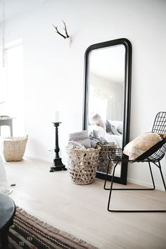 modern + bohemian. Wire chair and large angled mirror by the closet