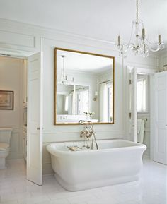 Chic, sun filled bathroom boasts walls accented in decorative moldings framing a large square gold leaf mirror hanging over freestanding bathtub paired with wall-mounted vintage tub filler flanked by a water closet to the left and a shower room to the right atop white staggered tiled floor.