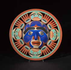 "A Nootka mask  Art Thompson, Nitinaht Lake, B.C., Oct. 1990, ""Bella Coola Sun Mask"", the central visage encircled by a corona of secondary faces flanked by upraised hands.  diameter 17 3/4in"