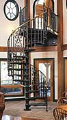 """5' 0"""" Diameter Victorian One Kit with optional double in-between spindles, scroll tread ends, 1-1/4"""" brass handrail with brass scroll handrail end, crowned princess design castings, custom over-sized landing and matching balcony landing rails. (Stair painted by owner.)"""