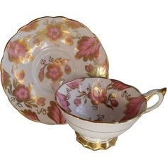 Commanding Royal Stafford teacup and saucer features deep pink florals and foliage heavy enhanced with gold on white ground. Thumbrest and spur.