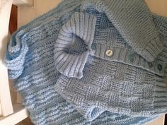 Image of pale blue baby cardigan and blankets