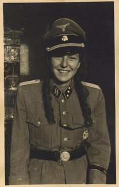 A young girl dressed in what is probably her father's uniform (as women could only be SS auxiliaries,) smiles for the camera.   The insignia on the cap indicates that the owner belonged to the SS Totenkopf Division, the most brutal and feared of the SS.  Most probably, this girl belonged to the Bund Deutscher Mädel/League of German Girls, the female version of the Hitlerjugend/Hitler Youth.