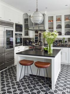 The kitchen includes a Sub-Zero refrigerator and a Wolf range and wall ovens; the antiqued-mirror backsplash tile is by Ann Sacks, the sink fittings are by Waterworks, and the stools are from Mark Jupiter.
