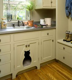 In the cabinetry, a kitty-shape opening to the cat-box area adds a touch of whimsy while keeping the cat-box private and out of view for guests.