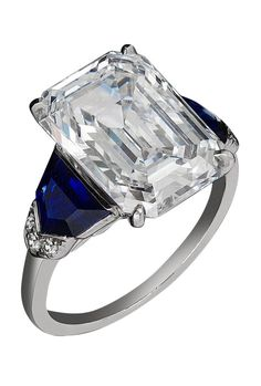 Raymond Yard - An Art Deco platinum, diamond and sapphire ring. Featuring a beautiful emerald cut diamond weighing 6.23 carats and boasting F color, IF clarity, and classified as Type IIa, this ring by Raymond C. Yard is enhanced with shield shaped sapphires and a trim of diamonds.