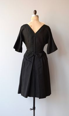 Vintage 1950s, early 1960s black silk faille cocktail dress with bateau front neckline, V back, 3/4 sleeves, fitted waist, back bow, full skirt and metal back zipper. --- M E A S U R E M E N T S --- fits like: medium bust: 39 waist: 28 hip: 40 length: 41 brand/maker: n/a condition: excellent to ensure a good fit, please read the sizing guide: http://www.etsy.com/shop/DearGolden/policy ✩ layaway is available for this item ✩ more vintage dresses ✩ htt...