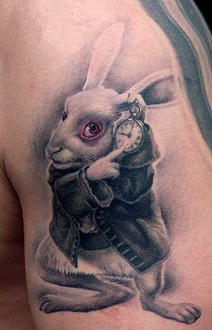 Тату на плече парня - заяц с часами