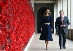 Donning a flowing navy blue dress complete with a tan belt, the brunette beauty stepped out alongside her husband