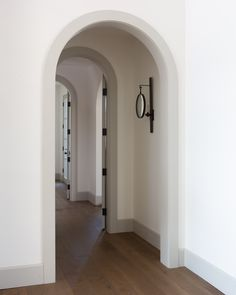 Jaimee Rose Interiors - Gray baseboards accent white walls and complement the gray moldings framing arched foyer doorways lit by Suzanne Kasler Alice Sconces. Arched Interior Doors, Arched Doors, Arch Interior, Interior Trim, Interior Architecture, Interior And Exterior, Painting Baseboards, Painting Trim, House Painting