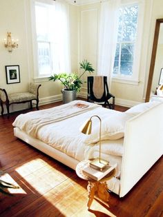 White bedroom with wood floors, indoor plant, and Victorian bench