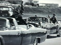 Secret Service agent George Hickey is seen brandishing a rifle in the followup car as the limousine carrying a wounded President Kennedy, with agent Clint Hill on back, heads to Parkland.