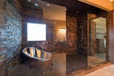 large glass and stone shower with silver tub