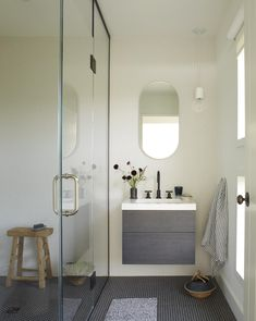 A small bathroom with shower serves the upstairs social spaces (the living room and kitchen). The wall-mounted vanity is from WetStyle and the wall and floor tile is Ann Sacks.