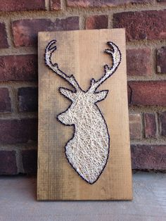 Rustic Buck String Art Wood Sign  Great addition to any home decor design!  Measures 17 inches tall 7 inches across  I have options for you to choose a stain color and a boarder color!  The item in this picture is stained with a special walnut stain and has dark blue colored string for the border. Comes with a bracket on the back for immediate hanging!  Will ship within two days of order using the USPS 2 day priority shipping.