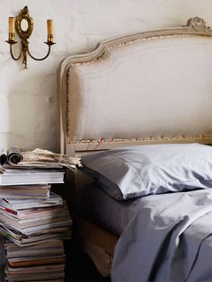 Love the headboard and sconce. And, naturally, the large stack of publications.