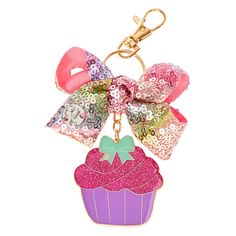 <P>JoJo Siwa is back and it's her Birthday! To celebrate she has created a super cute Birthday collection that has been covered in brightly coloured sequins so that you sparkle from head to toe! This mini rainbow sequin Birthday bow has been attached to a gold tone keyring and features a pretty Birthday cupcake in purple and pink glitter that drops down. It is the perfect accessory to hang from your bag or your keys! </P><UL><LI...
