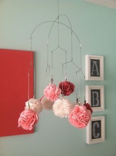 DIY rosette nursery mobile using a wire hanger from @Amazon.com.com. Adorable!