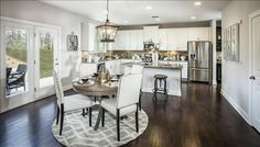 An open kitchen and dining area make an ideal place to entertain or relax with family. The Amelia plan, a new home by Beazer Homes at Kensington. Auburn, GA