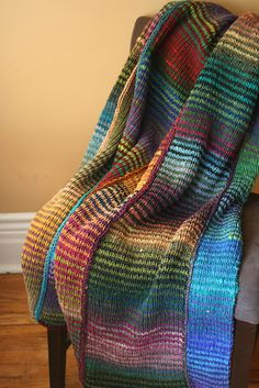64 Crayons Blanket. 2-row stripes knit with a self-patterning yarn. Blanket knit in strips that are joined at the end.
