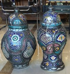 """Moroccan ceramic jars with wire filigree outlining vibrantly colored panels of traditional North African floral and geometric decoration. Hand thrown and hand decorated in Morocco. 14"""" x 22"""" and 11"""" x 23""""."""