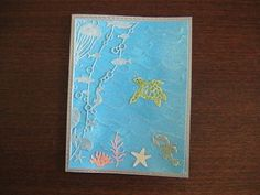 Dylusions painted background with  Fiskars embossing plate. Memory Box Oceana corner die and Frantic Stamper turtle, lobster, starfish, sponge and grass dies.