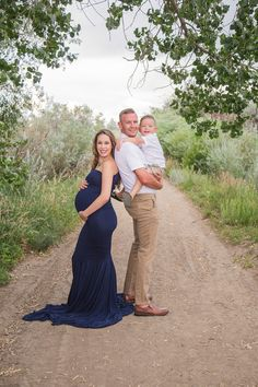 Family maternity session outside with green trees and mom in beautiful navy gown.