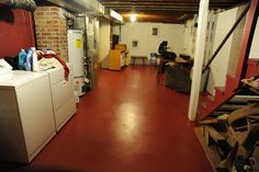 Freshly painted basement floor, clean clothes, rafters, brick chimney, washer and dryer, water heater, central heating system, tables, rolle...