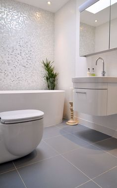 Love love love the Mother of Pearl tile on the wall with the light grey floor tiles, awesome feature wall and white everywhere else. www.subwaytileout...