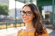Portrait of carefree young woman smiling and looking at camera with urban background. Cheerful latin girl wearing eyeglasses in the city. Happy brunette woman with long hair and spectacles smiling. How To Treat Pcos, Celebrity Smiles, Stained Teeth, Prescription Glasses Online, Kids Sunglasses, Cosmetic Procedures, Designer Eyeglasses, Cosmetic Dentistry